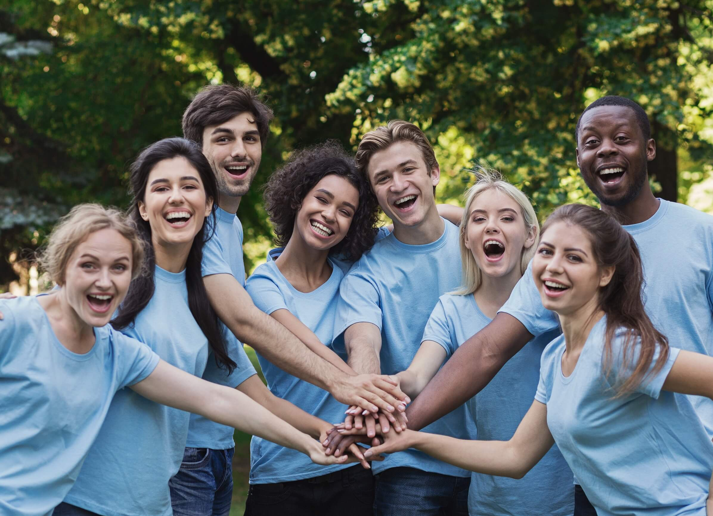 Smilende unge mennesker i lys blå t-skjorter holder hender oppå hverandre.