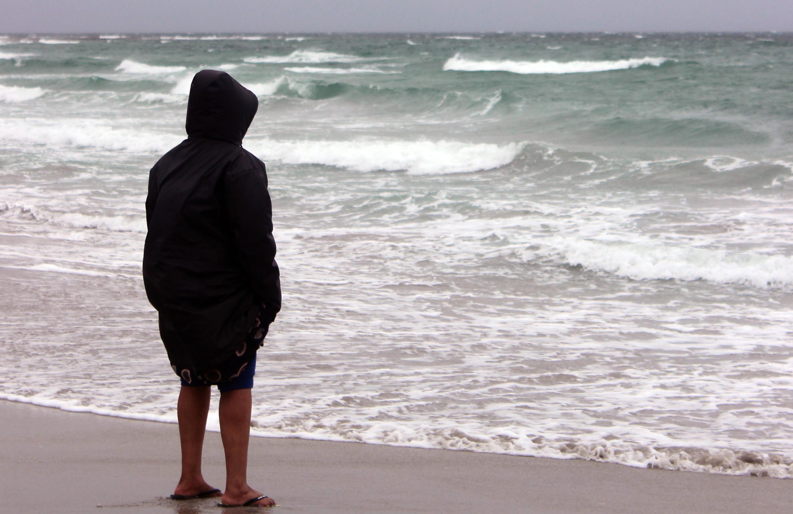 Kvinne står ser utover havet.