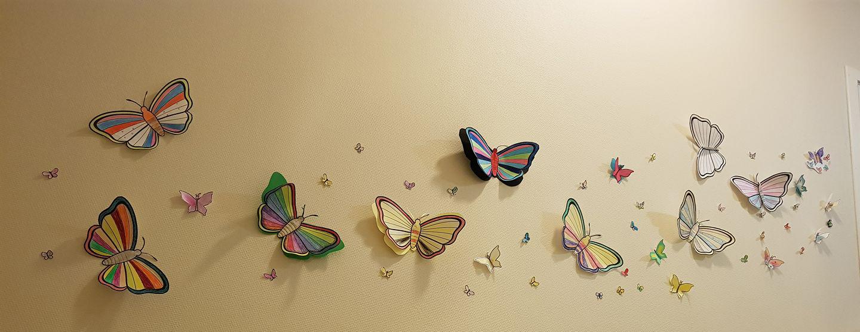Utklippet sommerfugler i papir på vegg.