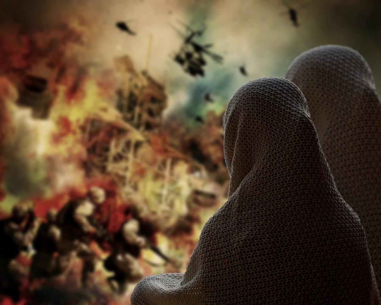 Kvinner tildekket med pledd ser på veggmaleri om krig.