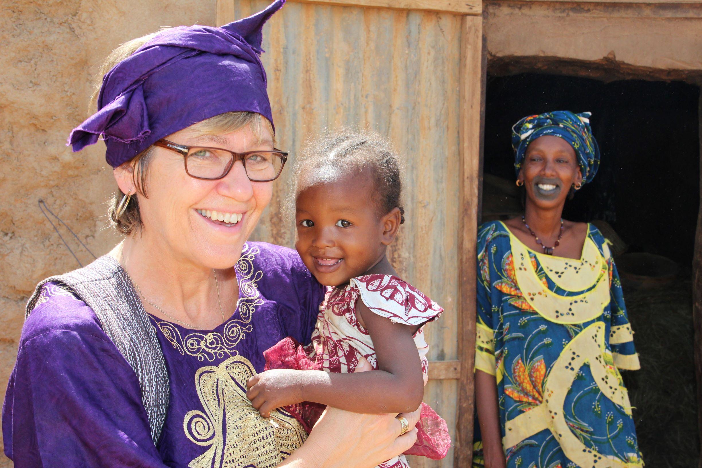 Norsk kvinne holder et mørkhudet barn i Afrika