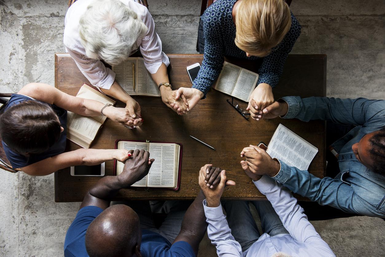 En gruppe menn og kvinner sett ovenfra holder hender rundt et bord
