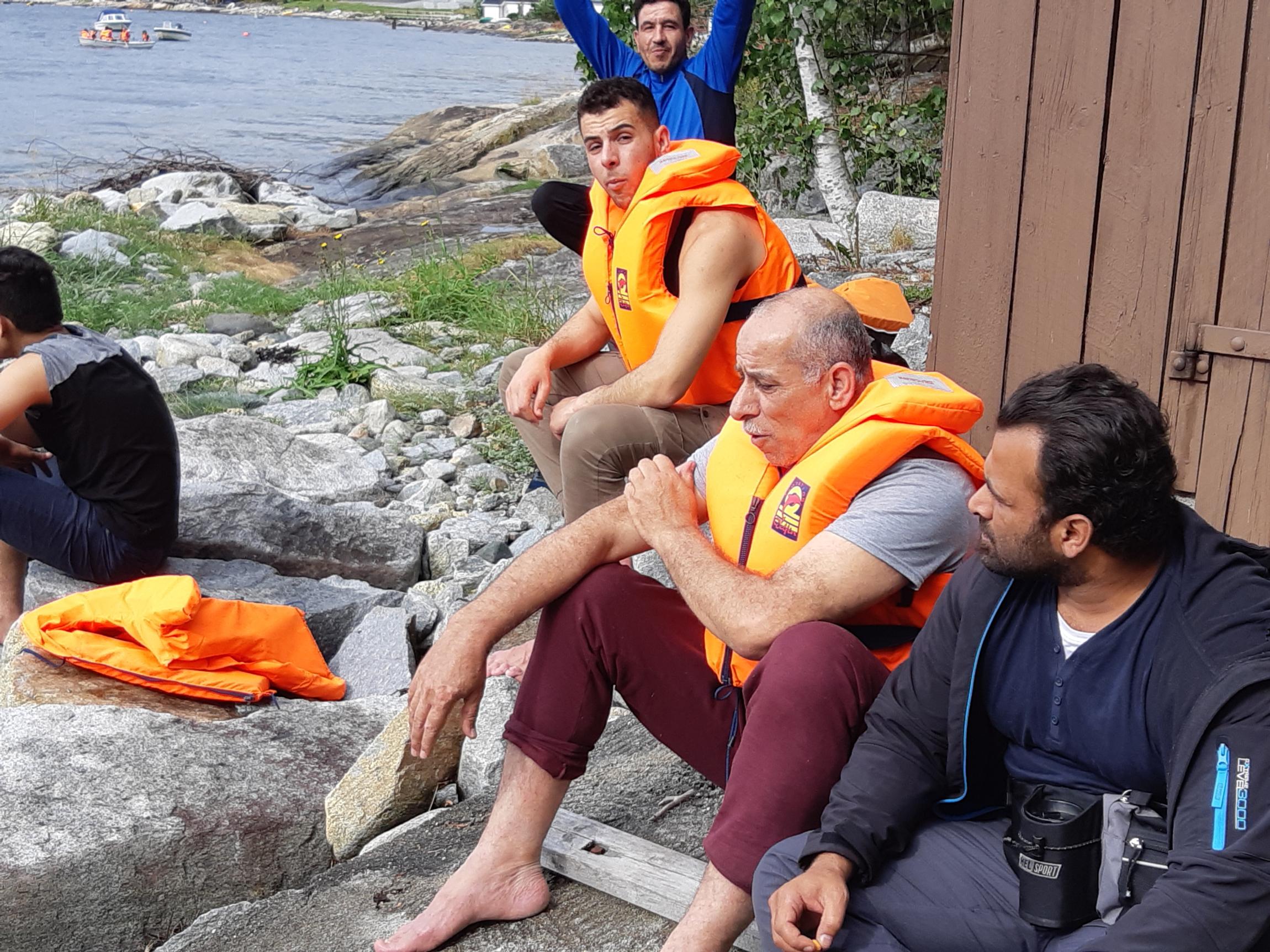 Menn i redningsvest sitter ved sjøkant