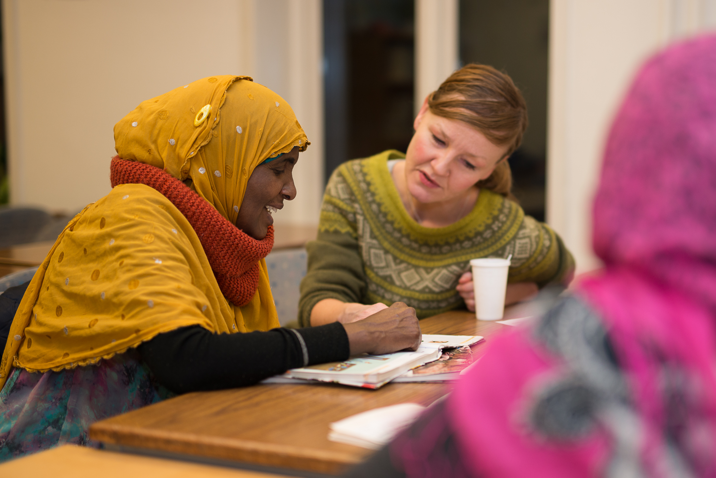 Innvandrerkvinne med lærer ved et bord