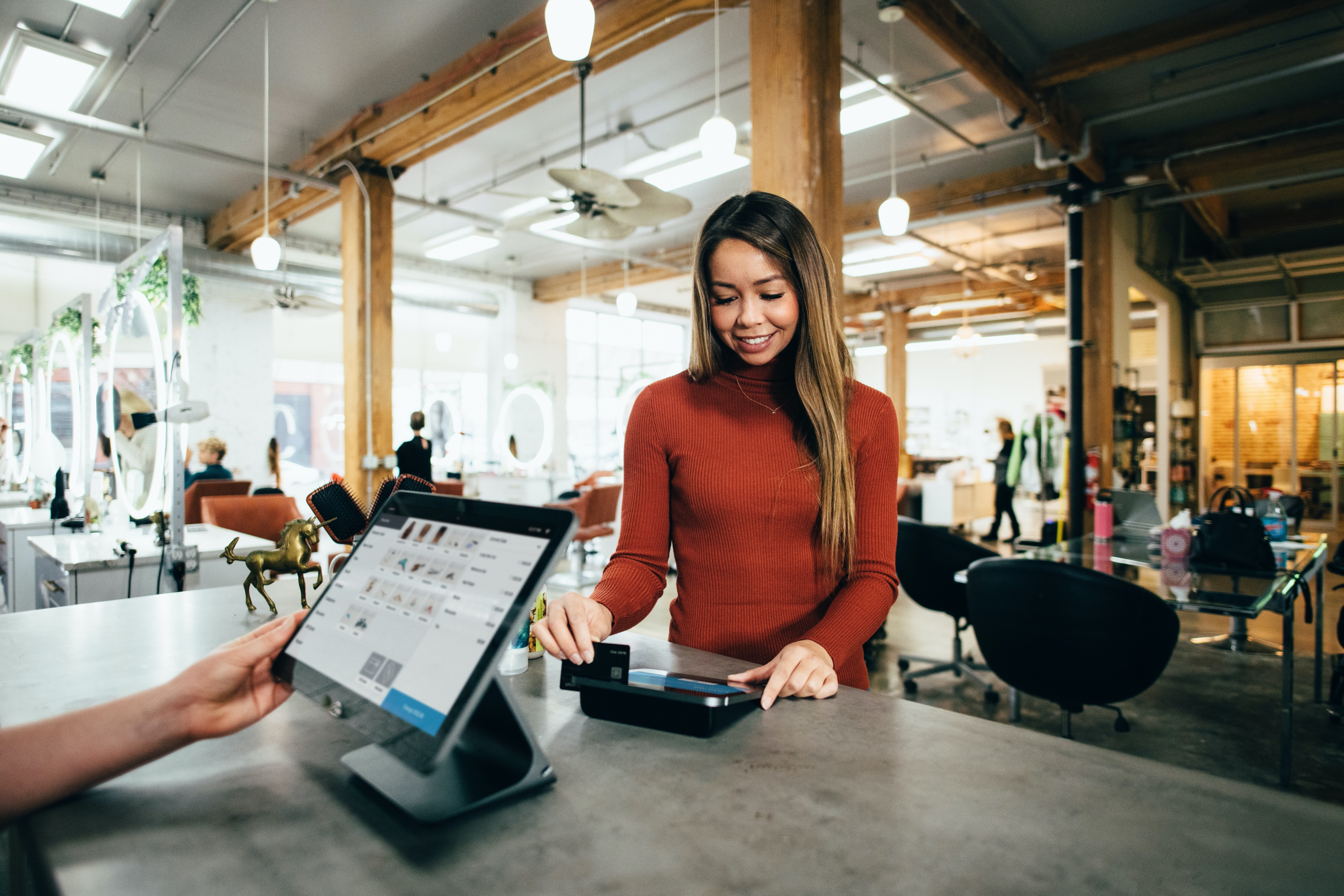 photo of women buying something using a modern point of sale device