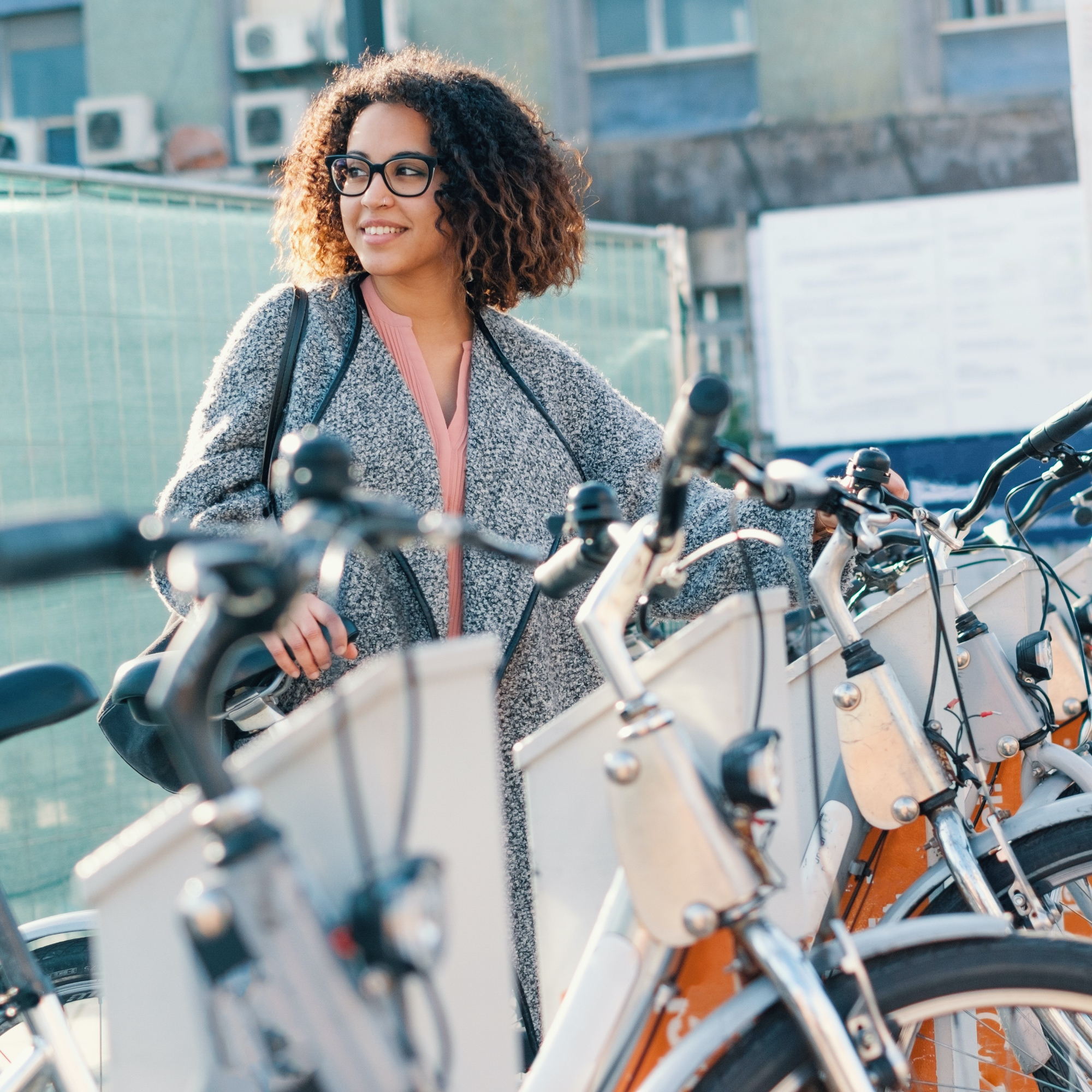Young woman in glasses standing by a line of sharable bikes.