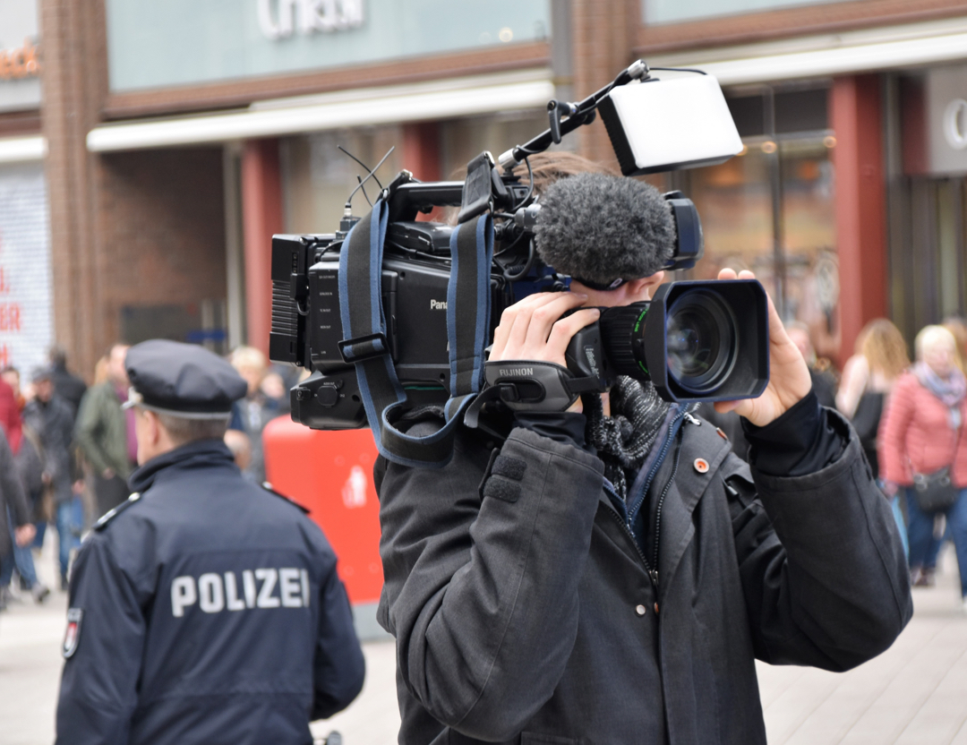 photo of a cameraman filming on the street