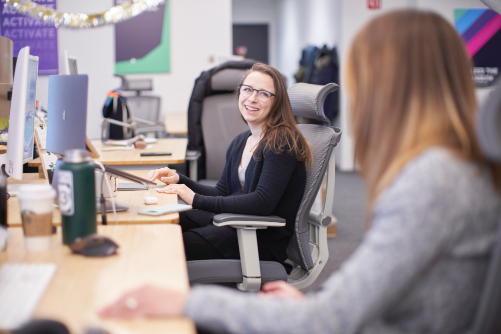 Hologram employees chat at their desks