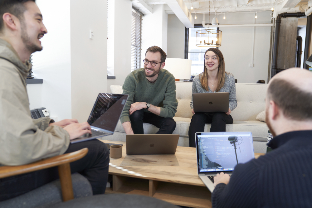 Hologram employees sitting with each other talking during a meeting