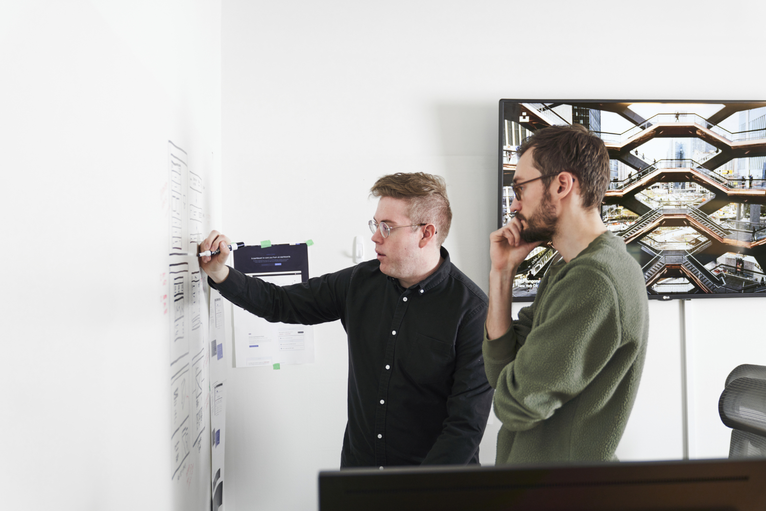 Hologram designers sketching wireframes on a whiteboard