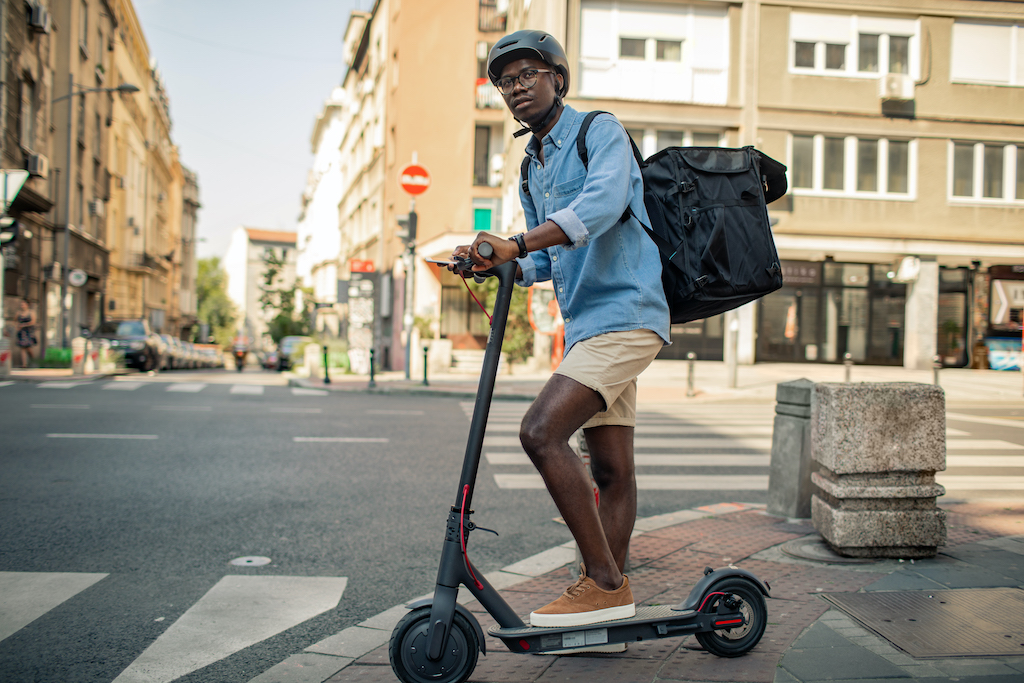 photo of a man using an escooter to deliver products
