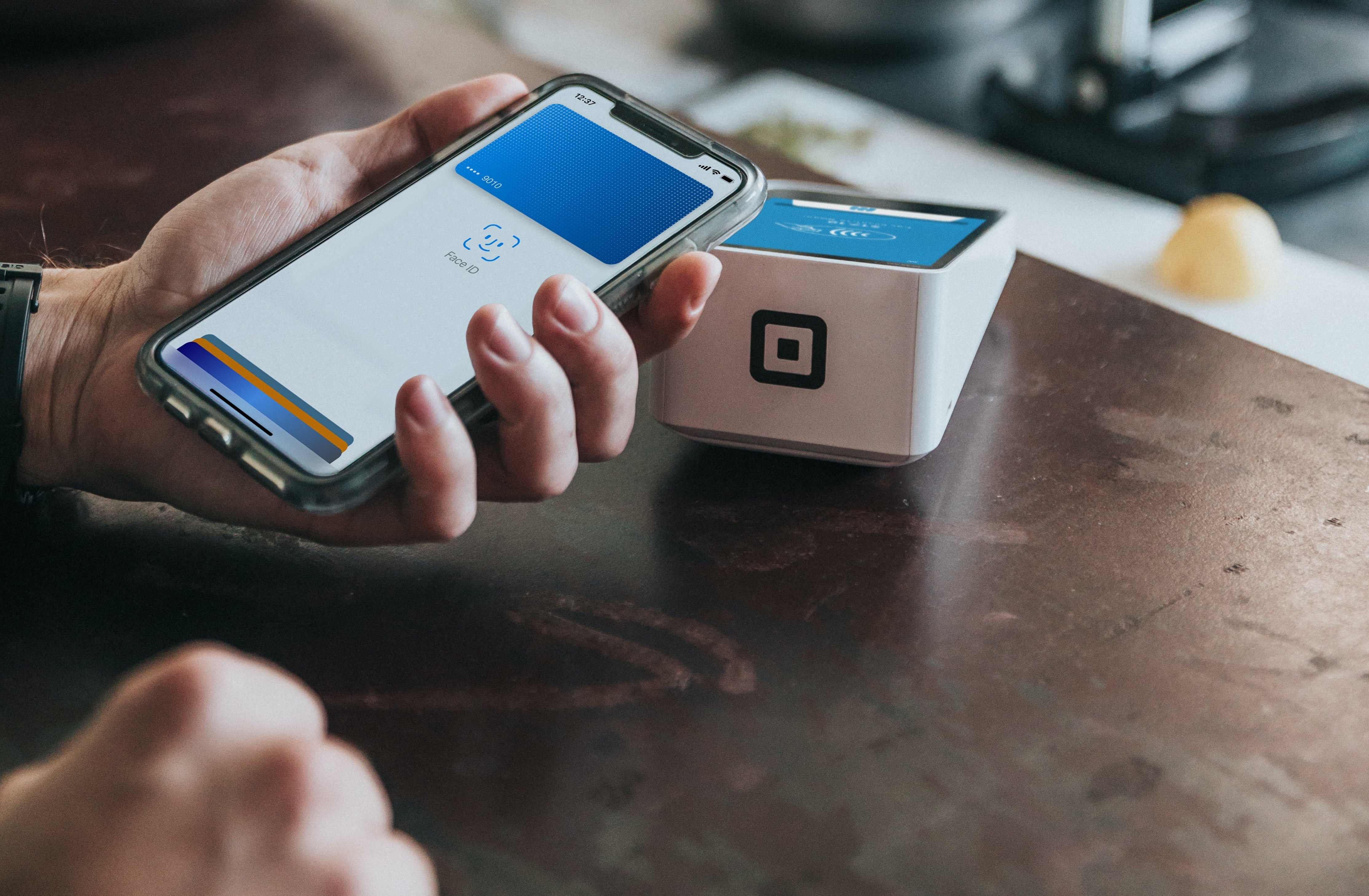 photo of person using apple pay on an iphone to pay using a credit card terminal