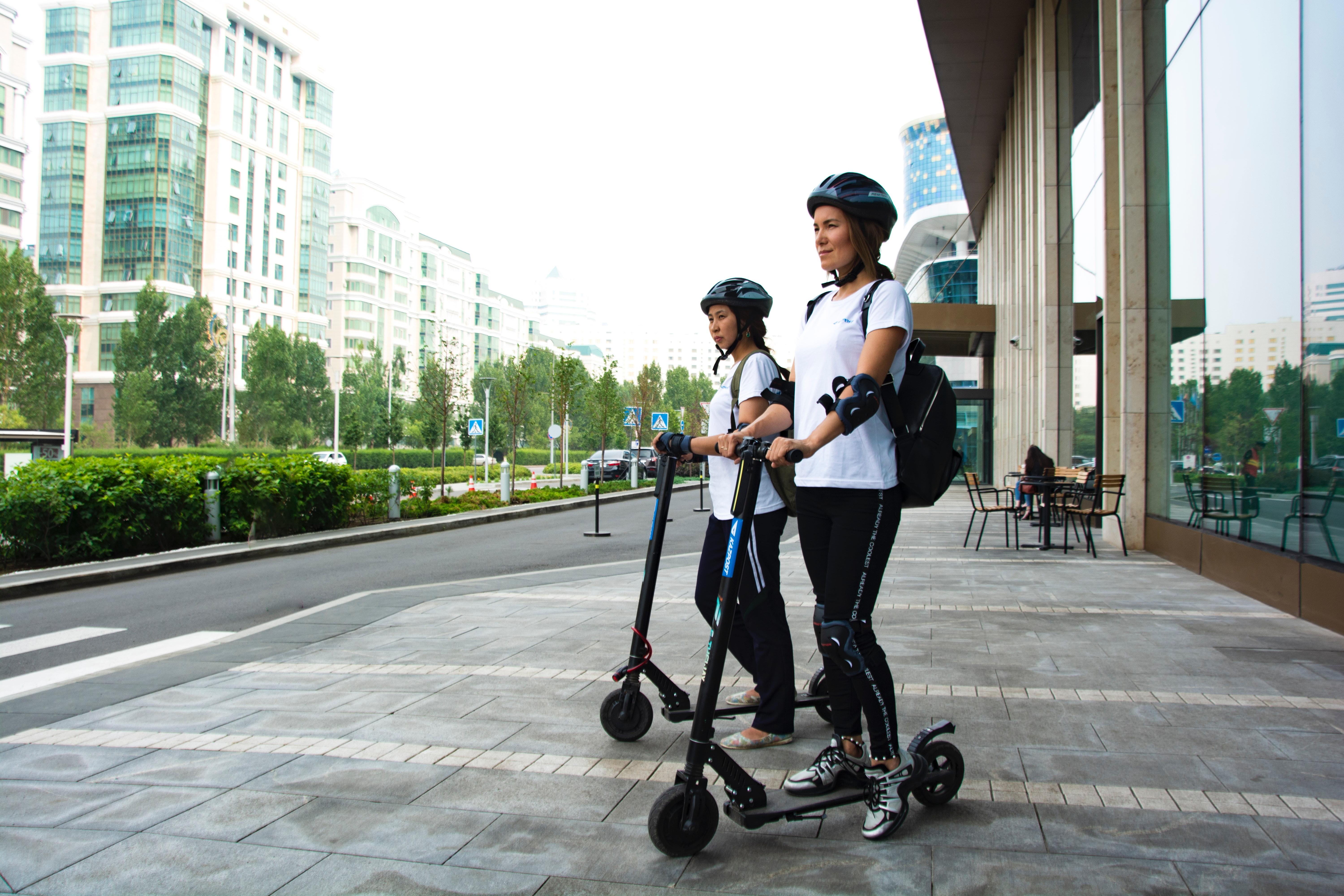 photo of two people riding scooter