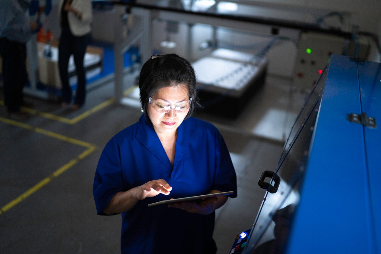 A woman oversees manufacturing from a tablet
