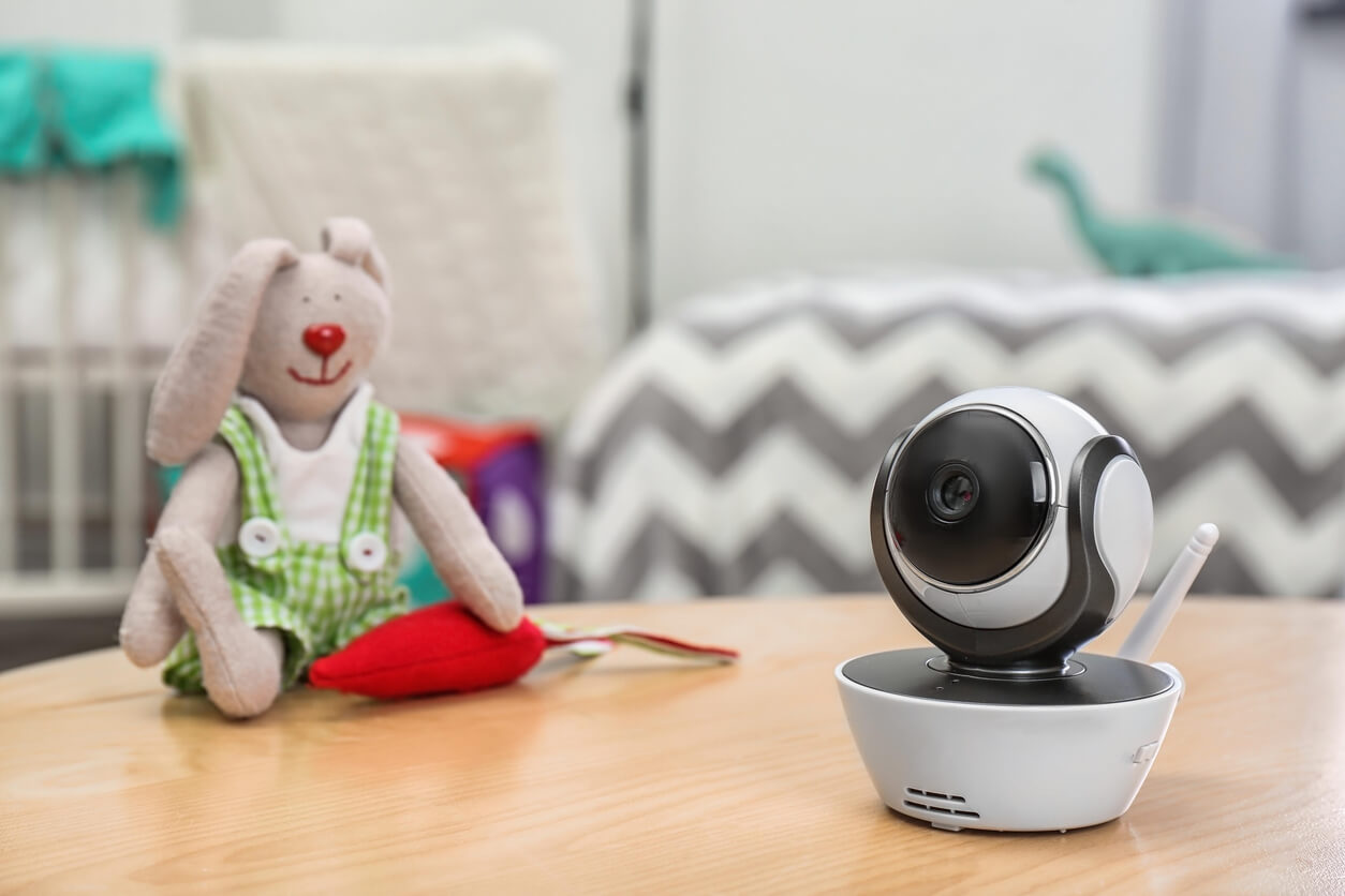 A smart baby monitor camera sits on a table next to a child's toy