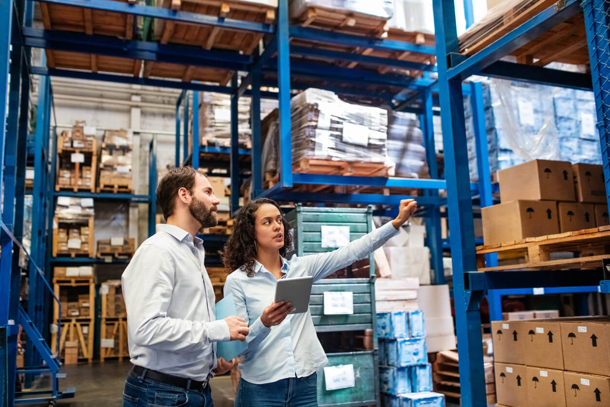 A woman with a smart tablet shows a man around an inventory warehouse/