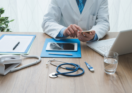 Doctor sitting in front of a laptop using a cell phone
