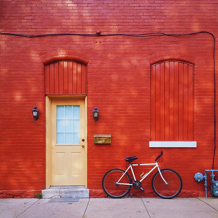 Vibrant red wall with a bicycle propped against
