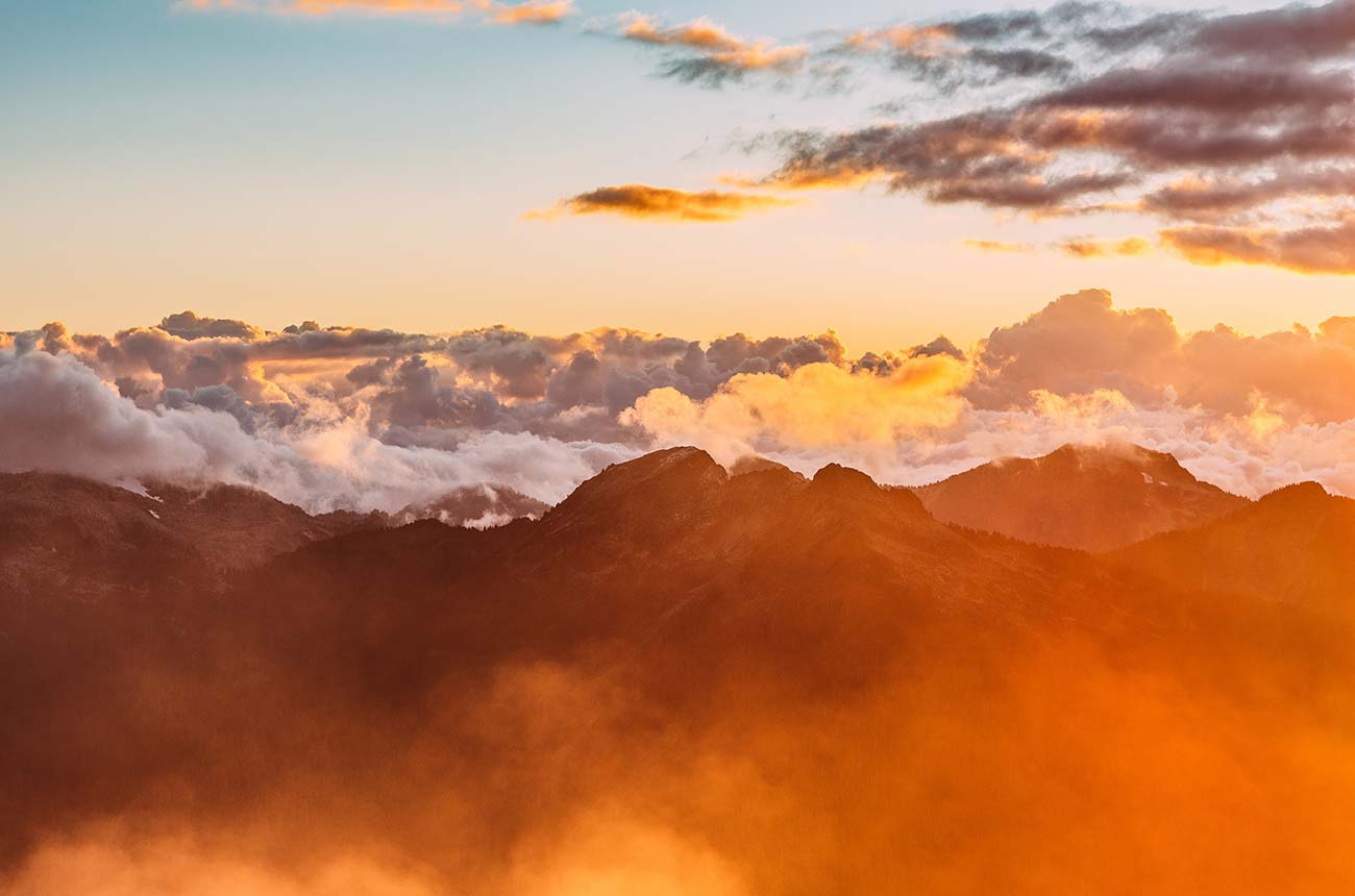 Sunrise over mountains with clouds & fog