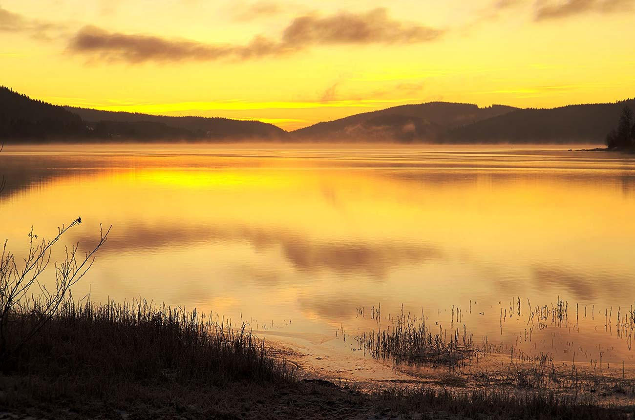 Sunsetting over a lake with mountains in the distance