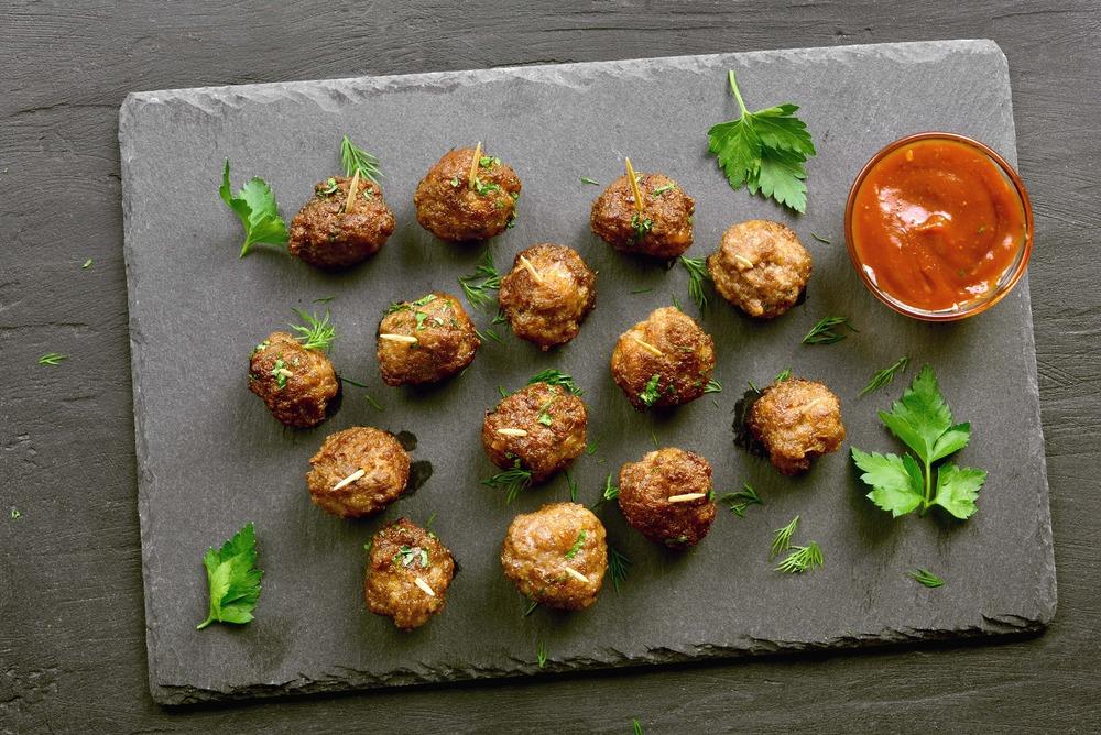 Sur une table en bois foncé est déposée une plaque de cuisson avec quatorze petites boulettes à base de quinoa et de dinde.
