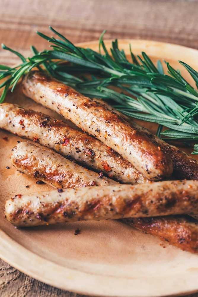 Sur une assiette en grès, à coté d'une branche végétale qui donne un côté champêtre à ce plat, se trouve quatre saucisses grillées appétissantes.
