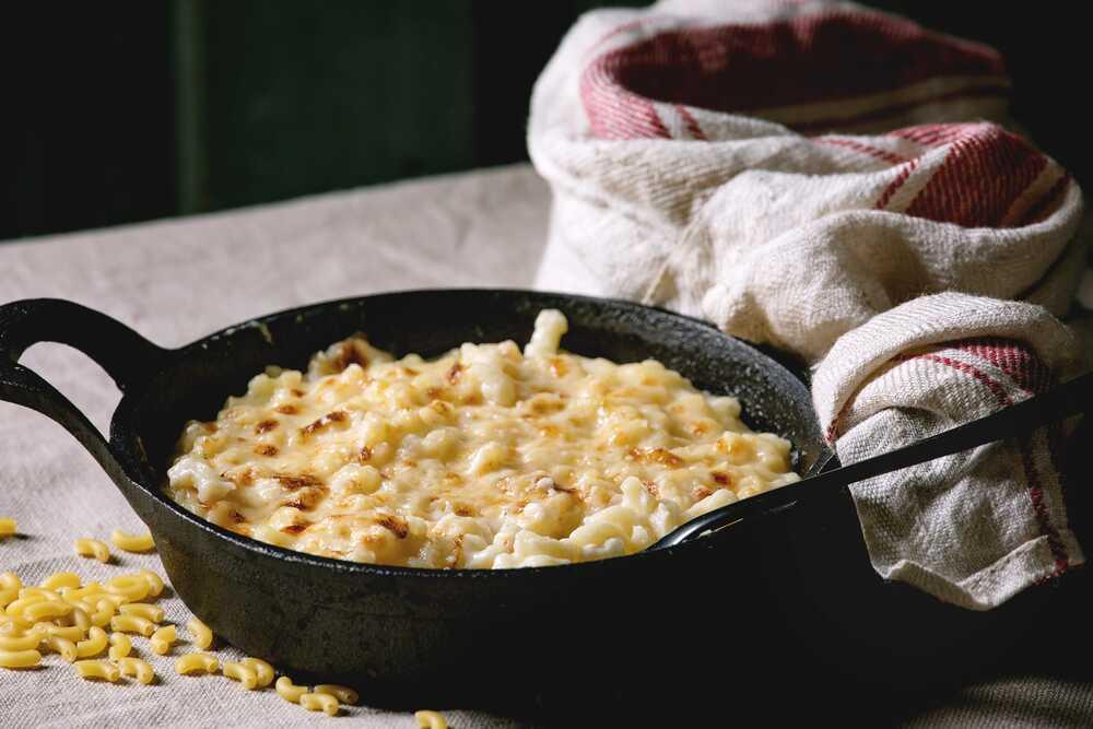 Présenté dans un gros caquelon en fonte de couleur noir, les coquillettes jambon et fromage sont légèrement gratinées.