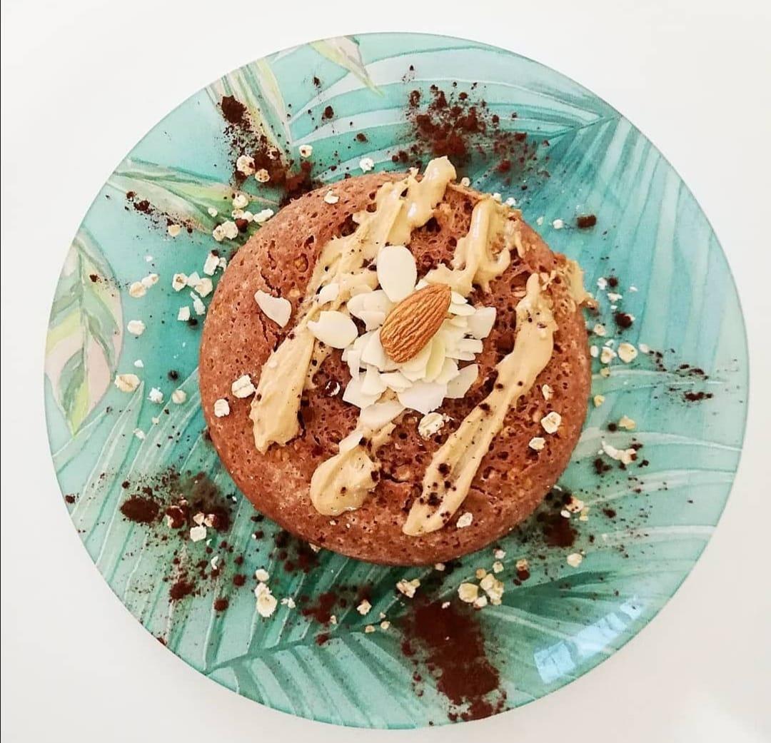 Sur une assiette bleue et blanche avec des motifs de feuillage, se trouve le bowl cake avec un saupoudrage de chocolat et des amandes concassées.