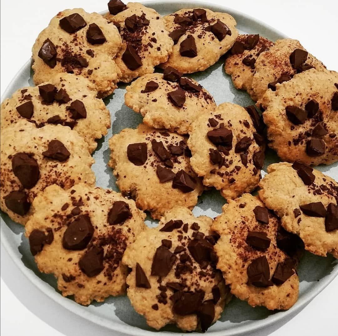 Sur une grande assiette de couleur bleue clair, quatorze cookies avec des pépites de chocolat sont prêts à être savourés.