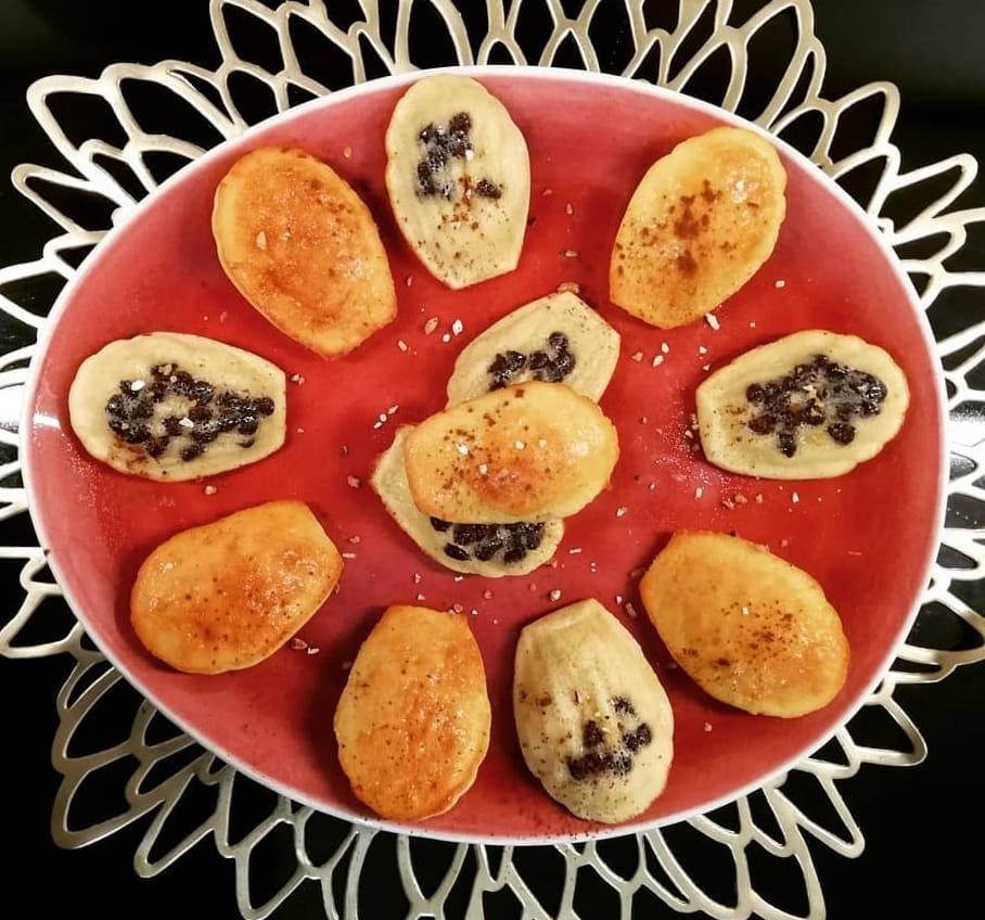 Disposés sur une assiette de couleur orange, six madeleines bien dorées sont coupées en deux. Les petites de chocolat sont bien présentes.