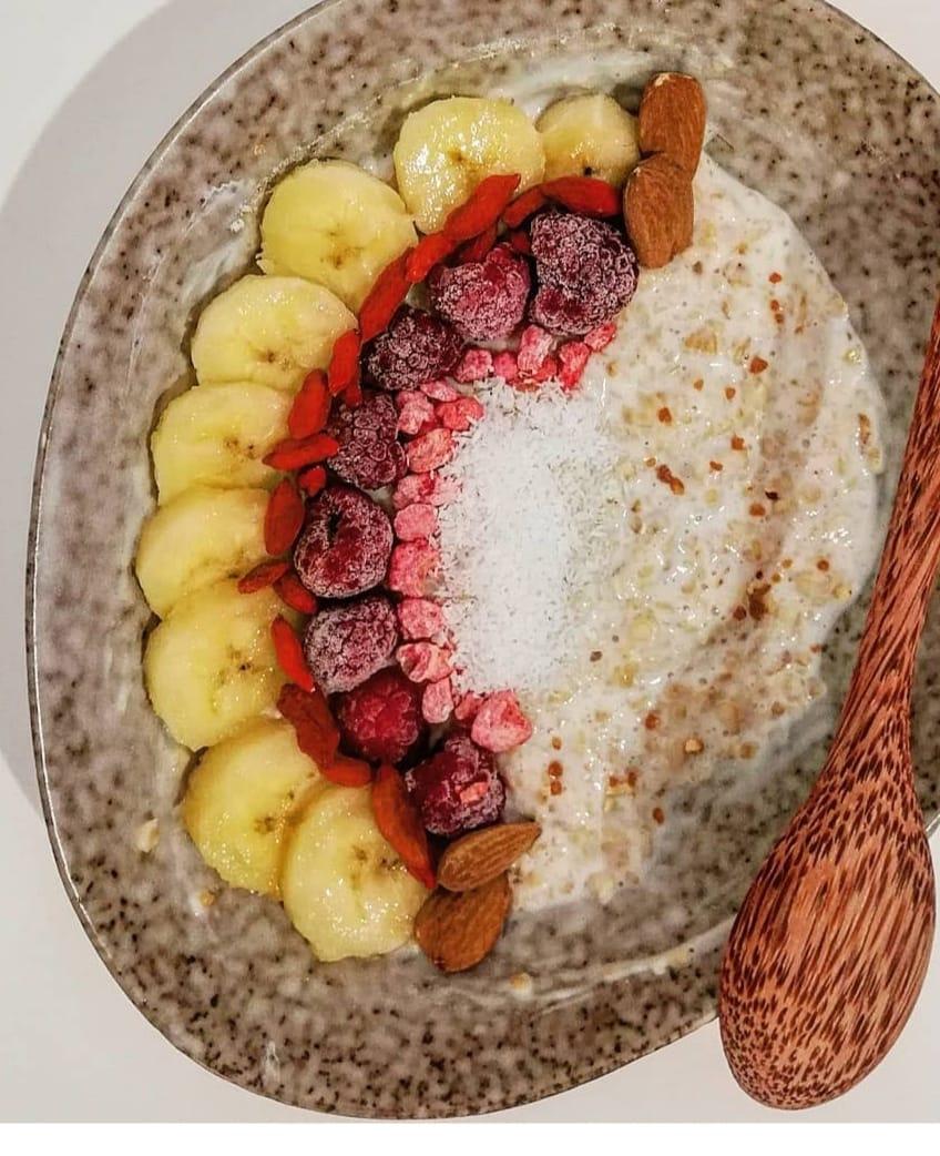 Dans un plat ovale en faïence de couleur beige le porridge est recouvert à moitié par de fines tranches de banane, quelques fruits rouges et amandes.s