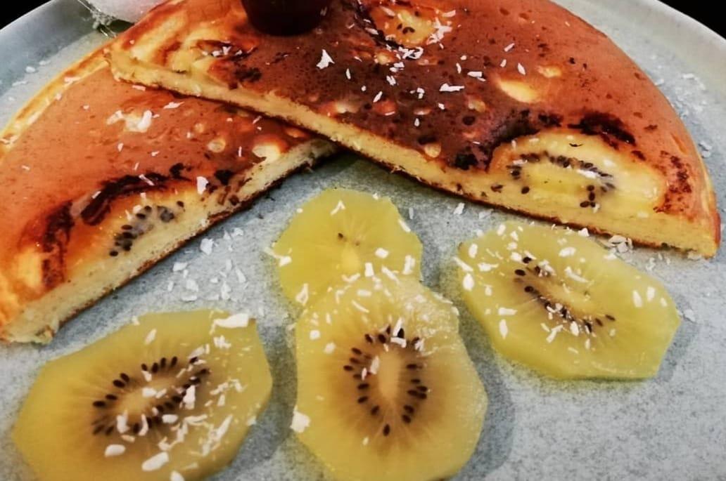 Un Pancake géant coupé en deux laisse apparaître les rondelles de kiwi. A côté se trouve quatre tranches de kiwi avec du coco finement râpé au dessus.