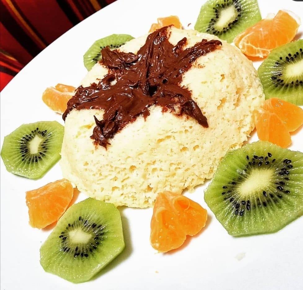 Le cake à la vanille est déposé au centre d'un plat ovale. Tout autour, des petites tranches de kiwi et des morceaux de mandarine sont disposées.