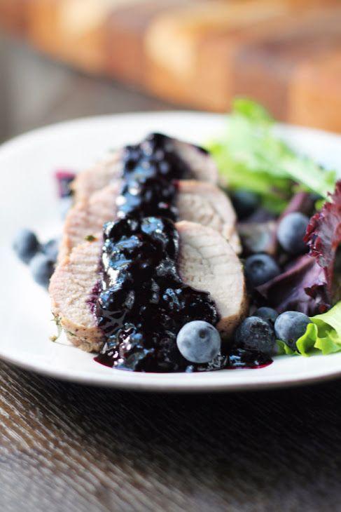 Sur une assiette de couleur blanche, une tranche de rôtie de porc est recouverte de la sauce aux myrtilles. Des myrtilles entières sont visibles.
