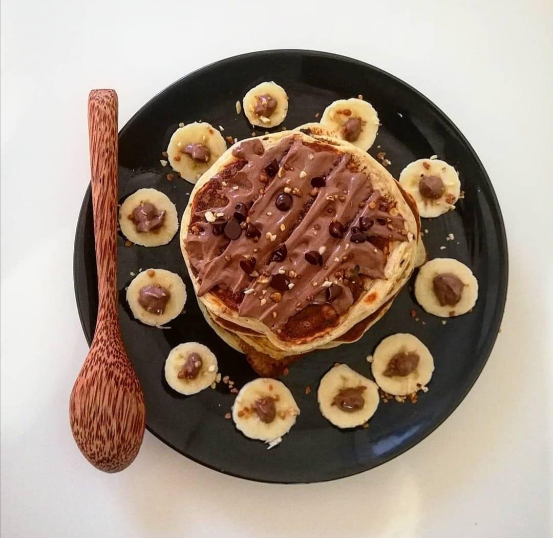 Sur une assiette de couleur noire, les pankakes sont empilés les uns sur les autres. De fines rondelles de bananes sont disposées autour.