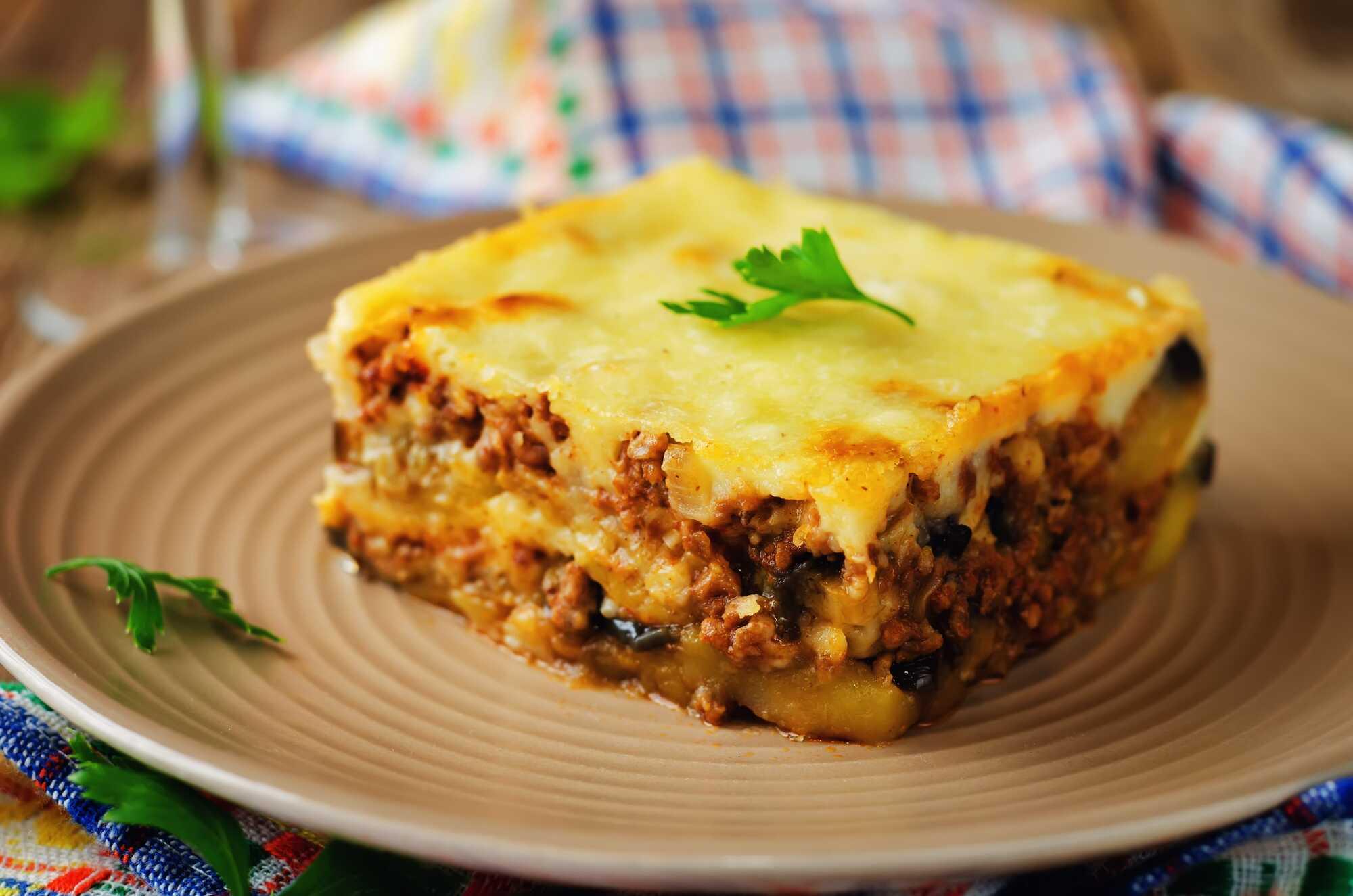 Sur un plat en grès beige, une grosse part de Moussaka avec ses différentes couches et par dessus le fromage gratiné.