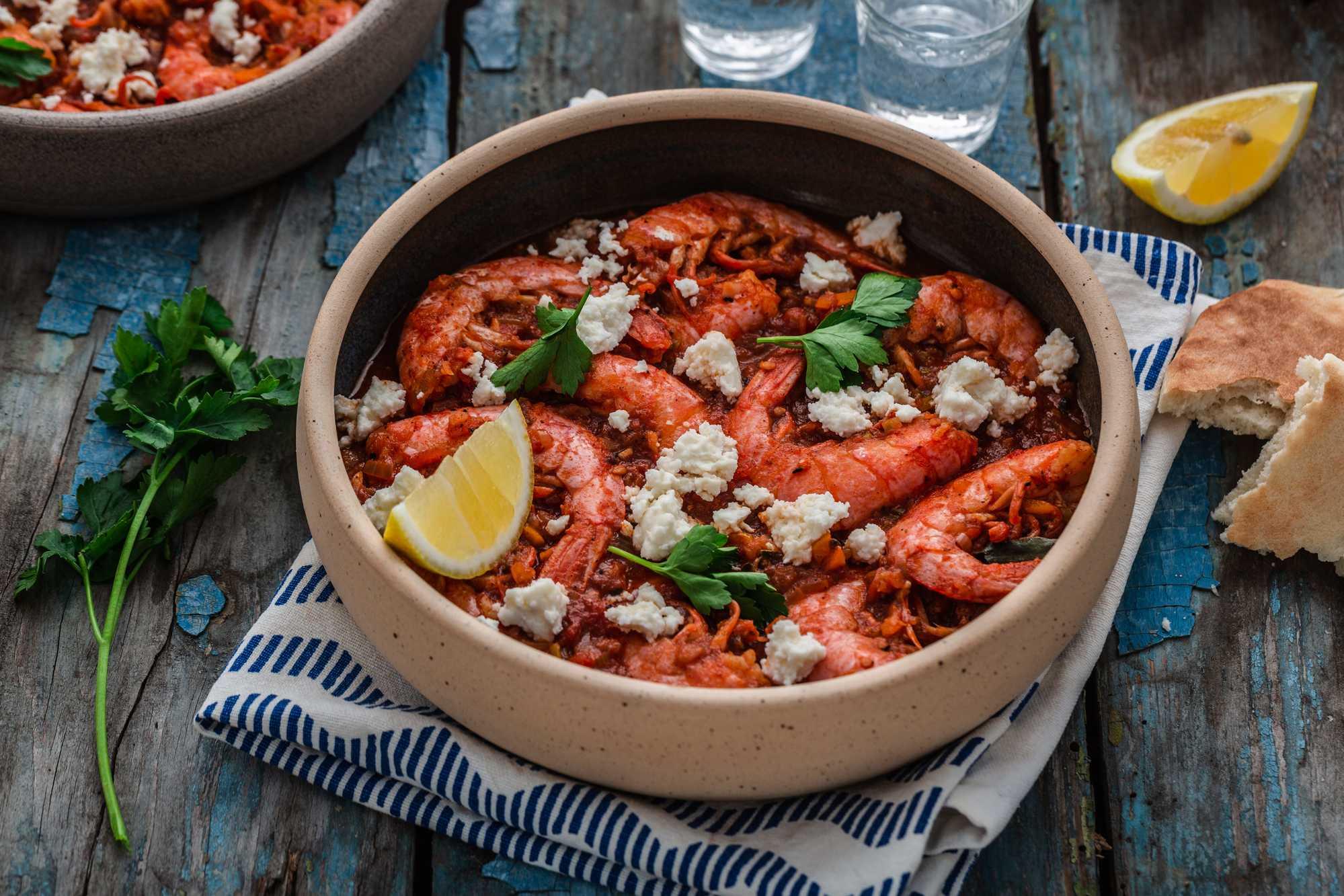 Les crevettes bien rouges sont présentées dans un large plat rond en terre cuite. Du persil et un quartier de citron jaune complètent l'ensemble.