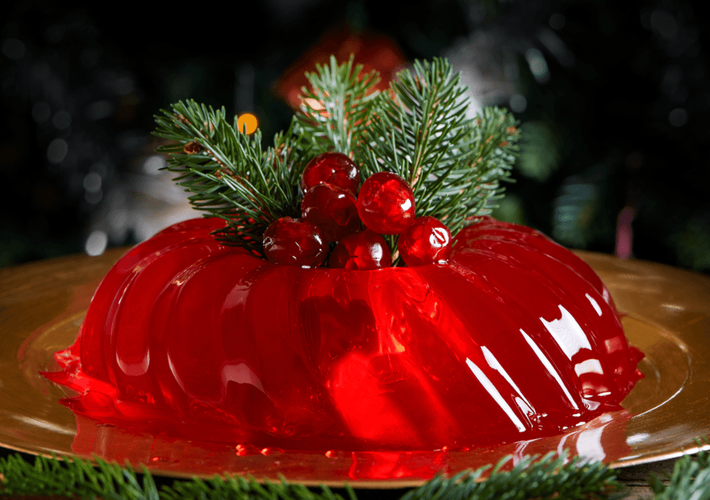 Sur une large assiette marron se trouve la gelée rouge grenadine. Le topping est assuré par des cerises confites et des feuilles de conifères.