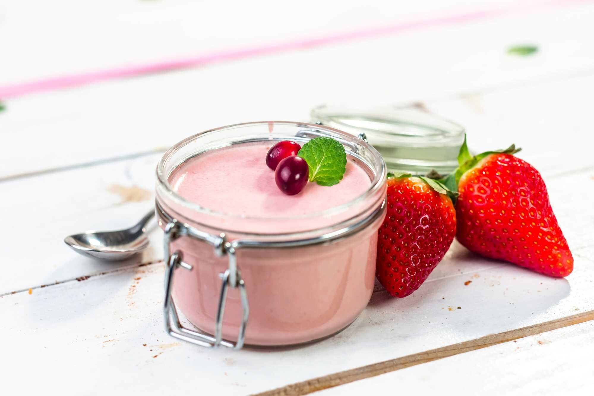 La panna-cotta est présentée à l'intérieur d'un bocal en verre ouvert qui sert à faire des conserves. Deux grosses fraises se trouvent à côté.