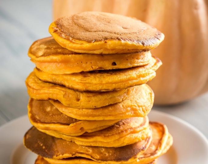 Des pancakes sont disposés les unes sur les autres dans une assiette blanche.