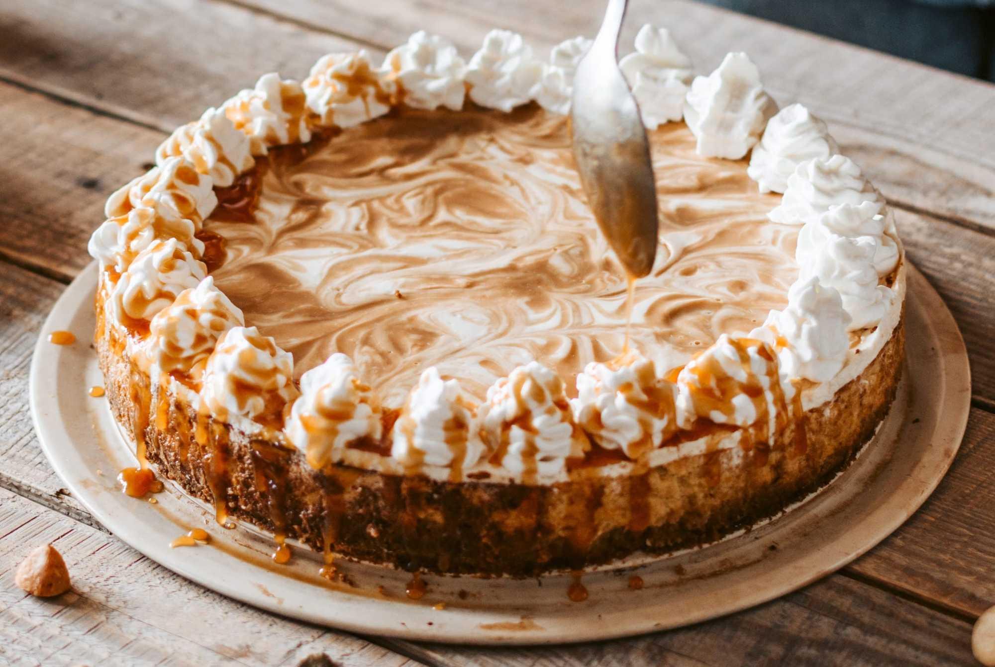 Un beau cheesecake est posé sur une grande assiette de couleur blanche. La crème chantilly disposée tout autour sur le dessus, sert de topping.