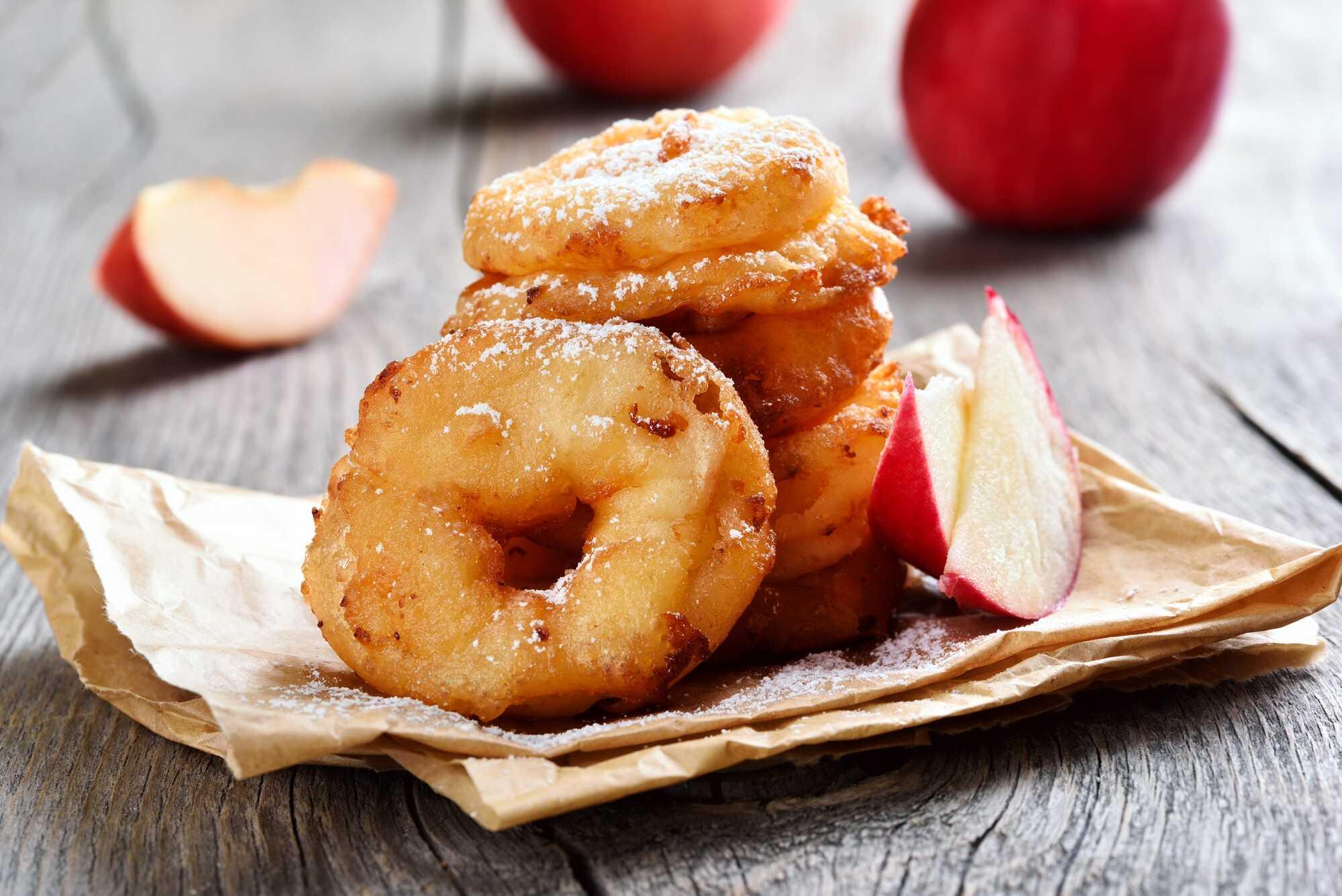 Quelques donuts reconnaissables avec leur trou au centre sont posés sur un sac en papier. Deux belles pommes rouges sont visibles également.