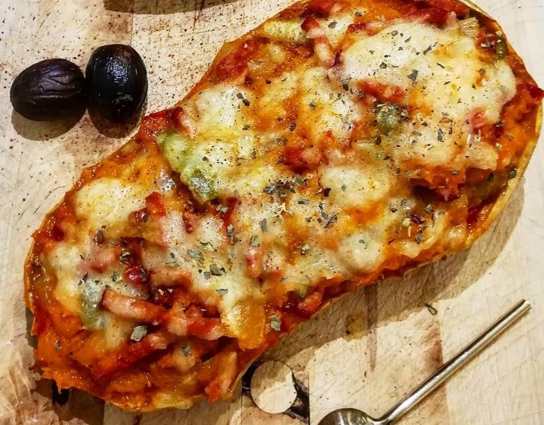 La peau épaisse de la courge sert de réceptacle à la préparation. Le fromage fondue complète la recette. Deux olives noires se trouvent à côté.