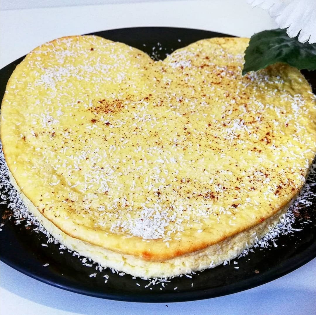 Présenté sur une grande assiette de couleur noire, le cheesecake en forme de coeur est saupoudré généreusement de noix de coco râpée.