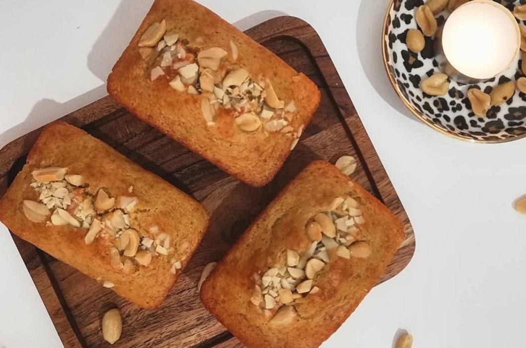 Sur un plateau en bois on trouve trois cakes de petites tailles démoulés, des cacahuètes concassés grossièrement sont parsemés sur le dessus.