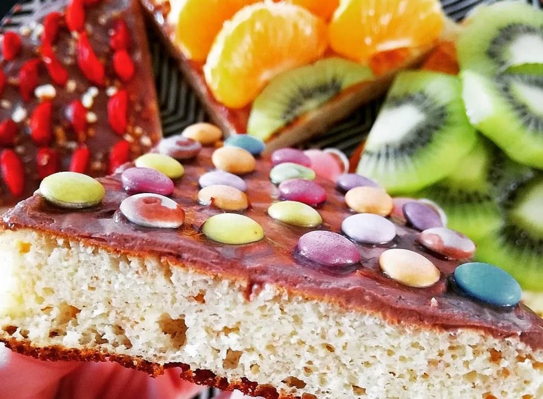 Sur le dessus de l'épais pancake sont disposés les smarties. Des tranches de kiwi et des quartiers de mandarine sont présents.