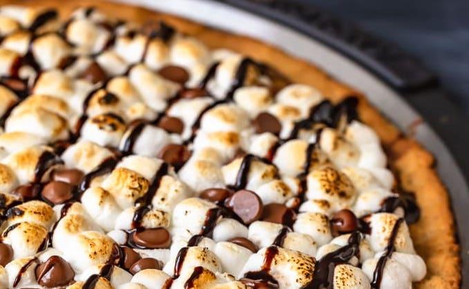 Encore dans son plat de cuisson, la pizza est recouverte de chocolat avec les marshmallows disposés avec application pour le plus bel effet visuel.