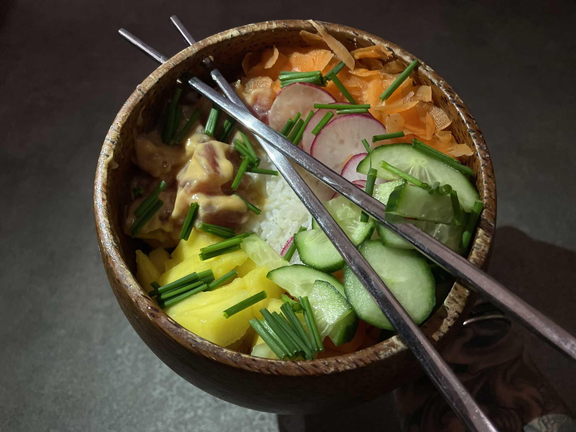 Dans un grand bol en grès , le riz est au centre et tout autour se trouve les différents ingrédients. Deux baguettes permettent de manger ce Poke.