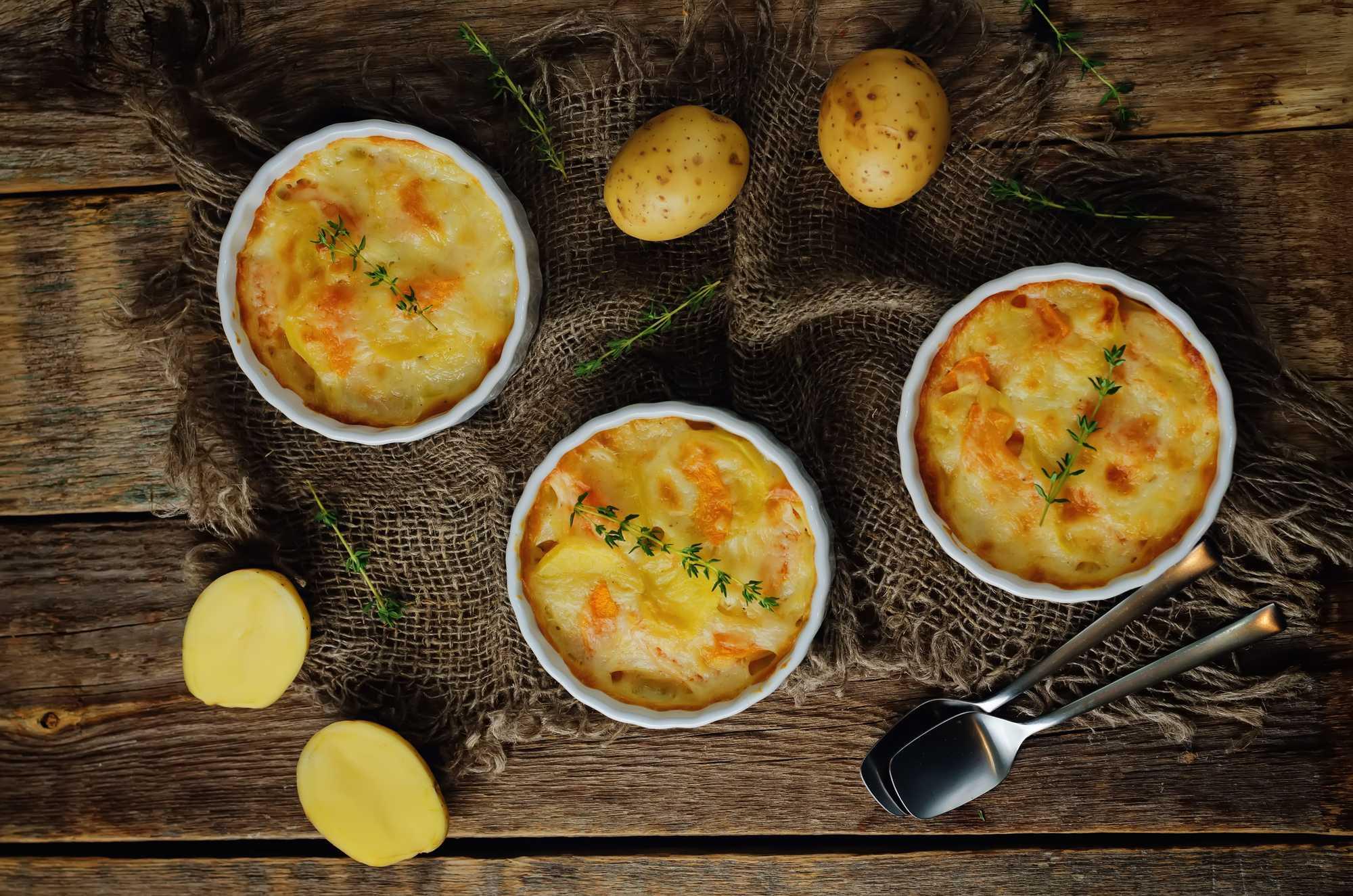 Présenté sur une table rustique, trois petits ramequins ronds contiennent ce Parmentier au saumon. Quelques pommes de terre sont disposées autour.