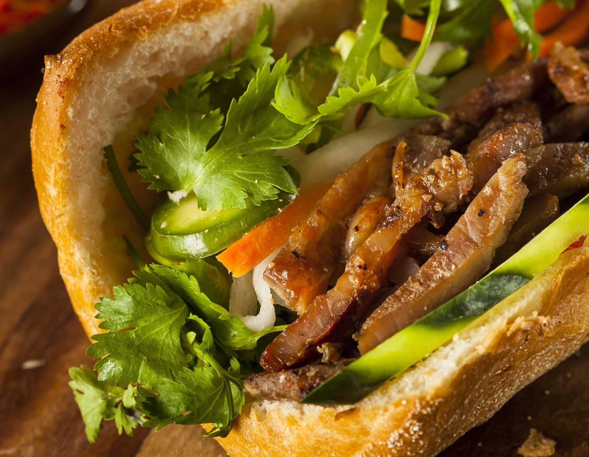 Dans une demi baguette ouverte se trouve le poulet bien grillé coupé en fines tranches avec les carottes émincées et enfin de la coriandre pour finir.